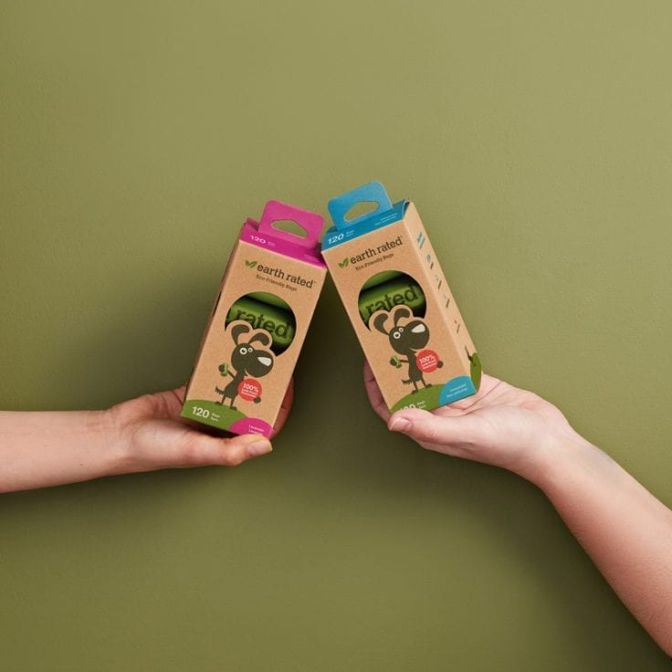 Two people holding up boxes of Earth Rated Refill Rolls